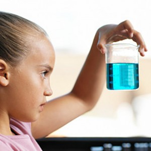 side profile of a little girl holding up a beaker holding a blue liquid